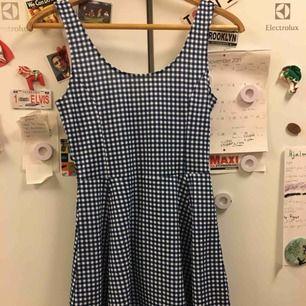 Kort klänning med slimmad överdel och något klockad kjol. Vitblå-rutigt mönster. Urringningen på baksidan går lite längre ner än den gör där fram. Väldigt bekväm och sval. I priset ingår inte frakt :)