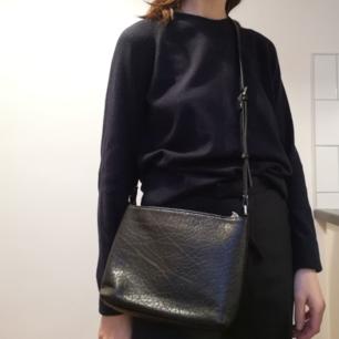 Svart handväska i läderimitation från Åhléns. Modellen påminner om Whyreds klassiska väska, men har en snygg ficka på ena sidan som gör den lite annorlunda. I superbra skick, blir tyvärr aldrig använd. Frakt 59 kr.