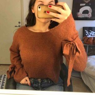 """Säljer min tröja från Berska då den inte kommit till användning. Den är brun/orange och jätte mysig. Armarna är utsvängda med """"rosetter"""" på som går att knyta själv. Köpt för 300kr."""