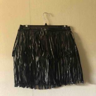 Svart kjol i läderimitation med fransar från H&M i storlek 38, aldrig använd med prislappen kvar. Pris 100kr