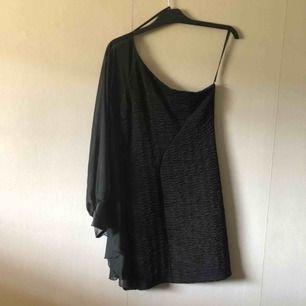 Svart klänning med en ärm som är i chiffong och med drapering mellan ärm och klänning, supersnygg på, använd på en fest, storlek M, 100kr