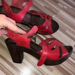 """Ett par snygga träklackar i äkta rött läder. Aldrig använda, vilket är synd:(. Inköpta på Scorett för 600kr, som man ser på bilden. Passar även 37, så man kan säga att de är """"små"""" i storleken. (Pris kan diskuteras) 😊"""