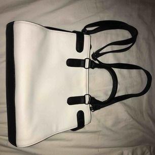 vit handväska med svarta detaljer💖✨ handtag + avtagbart axelband. köpt för ca 500kr men knappt använd. Remmen i mitten (bild 2) går att öppna på båda sidor så väskan blir bredare + får plats med mer.🥰 Hör av er om ni vill veta om väskans fack osv😘