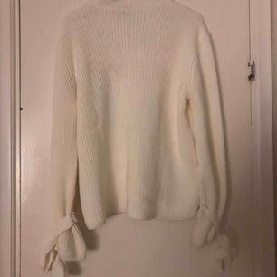 Frakt inkluderad. Fin stickad tröja från Gina med knytsaker runt ärmarna.