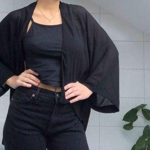 En cardigan i svart, tunt material som passar som både vinterplagg och strandplagg. Går över rumpan och är väldigt skön att bära!