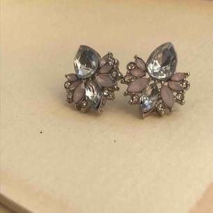Ett par silvriga örhängen med rosa detaljer. Köpta på Ur&penn. Kommer tyvärr inte till användning😊 köpare står för frakt. Skriv för mer info!!🥰