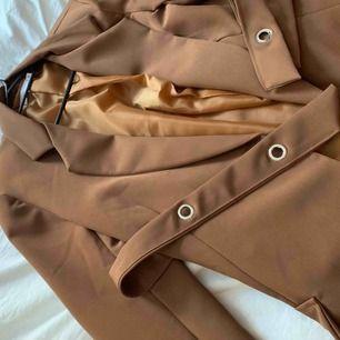 Oanvänd lätt oversize brun kavaj med tillhörande bälte. Utmärkt skick. Säljes då jag råka köpa för liten storlek.   Frakt ingår inte i priset. Kan hämtas i Stockholm.