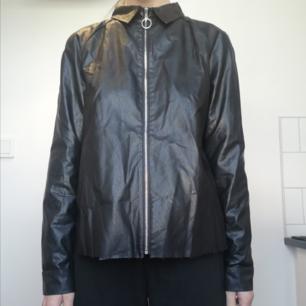 Svart faux leather skjorta från Zara i stl M. Snygg rund dragkedja och detaljerad rygg. Går att använda öppen som tunn skinnjacka också, säg till så skickar jag bild. Frakt 59 kr.