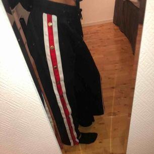 Svarta byxor med rand samt knäppning på sidan. Köpta på TESSIE, storlek M men är som XS-S.