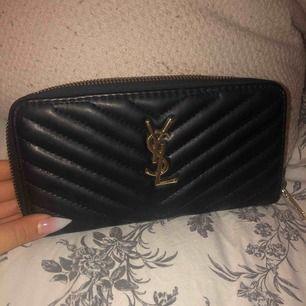 Fin YSL plånbok, köpt i Dubai. Dragkedjan går sönder ibland och går inte att knäppa, men detta går att fixa snabbt och billigt för köparen hos en skomakare. Plånboken är i gott skick!