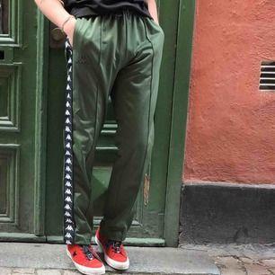 Gröna Kappa byxor med loggan på sidan. I sportmaterial typ. Waste går att justera och length 30. Inte skadade alls. Pris går att diskuteras.