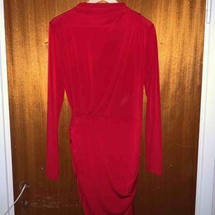 Röd klänning, tajt på underdelen och lite lösare vid brösten. Använd 1gång, från Gina Tricot. Slutar över knäna