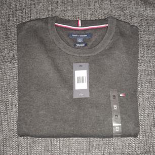 Helt ny tröja från Tommy Hilfiger Tröjan är naturligtvis äkta och med tags kvar.  Färg: Mörk grå Storlek: M