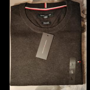 Mörk grå tröja från Tommy Hilfiger.  Tröjan är naturligtvis äkta och med tags kvar.  Färg: Mörk grå Storlek: L.