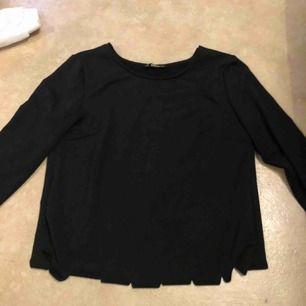 Svart långärmad tröja, räfflad nedtill och bak i ryggen. Den går omlott bak. Köparen står för frakt