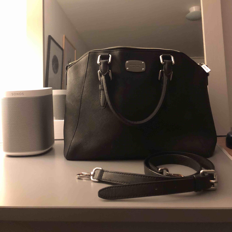 Svart, rymlig läderväska från Michael Kors med medföljande justerbart axelremsband Serienummer AL-1510 Väldigt fint skick men har några repor på brickan samt lite slitningar på axelbandet Kan gå ner i pris vid snabb affär:). Väskor.