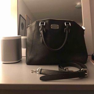 Svart, rymlig läderväska från Michael Kors med medföljande justerbart axelremsband Serienummer AL-1510 Väldigt fint skick men har några repor på brickan samt lite slitningar på axelbandet Kan gå ner i pris vid snabb affär:)