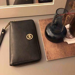 Svart Michael Kors plånbok i läder Fack för mobil, kort samt mynt finns Sparsamt använd Väldigt bra skick men metalldetaljerna är något repiga! Meddela för fler bilder:) iPhone plus får plats i mobilfacket