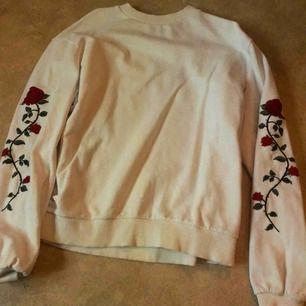 Vit sweater med röda rosor på ärmarna från na-kd. Köparen står för frakt och pris kan diskuteras