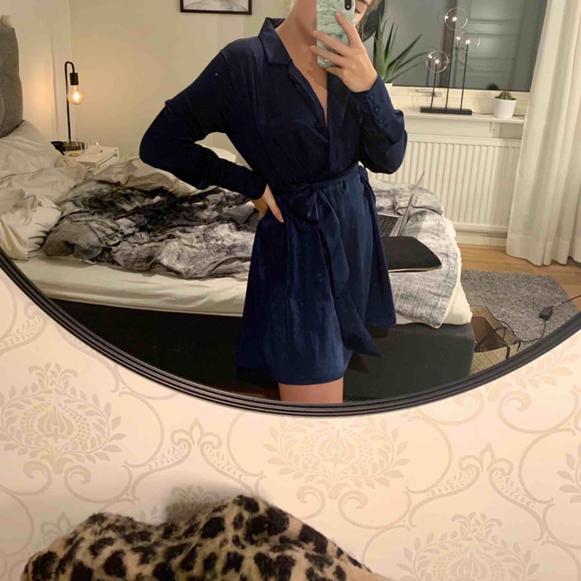 Säljer denna fina klänning då den endast hänger i garderoben. Klänningen är endast använd en gång och är därför i nyskick. Klänningen är marinblå och är i sidenliknande tyg.Strl M men passar även S. . Klänningar.