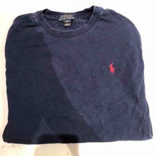 En polo T-shirt, väldigt enkel design med den polo-märket på bröstet. Storlek L för kids så skulle säga S - Xs för äldre. Kunden står för frakten :)