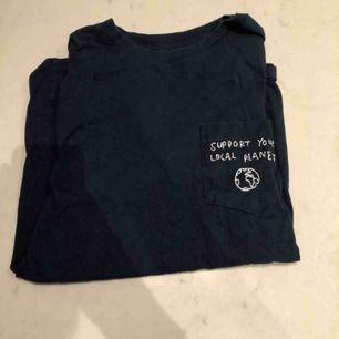 En mörkblå T-shirt köpt från T-shirt store på Götgatan. Storlek Xs men passar s -m. Väldigt bekväm med en härligt budskap på bröstet. Kunden står för frakten :)