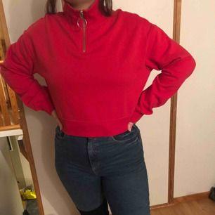 En vanlig röd tröja från h&m med dragkedja vid halsen. Storlek M