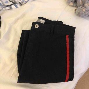 Svarta jeans med röd rand Möts i stockholm