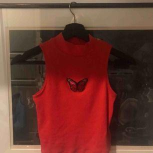Jättefin röd crop top med en röd/rosa fjäril på bröstet. Är i storlek XS men är väldigt stretchig så passar säkert någon som har storlek S också. Frakt ingår ej🦋