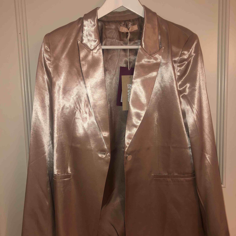 Guldig glansig kavaj från Nelly aldrig använd storlek 36. Kostymer.