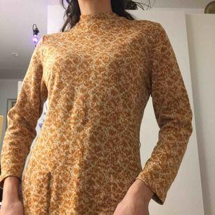 Orange/gräddvit vintage klänning med fickor i tjockt material. Litet i armhålan som lätt kan sys igen.  (っ◔◡◔)っ MÅTT: Byst: 47cm Längd: 103cm Ärm: 56cm