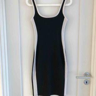 Svart knälång klänning med skulpterande vita detaljer från Zara. Storlek S.