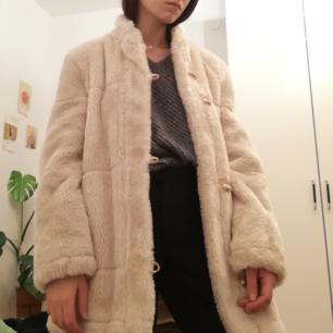 Krämvit vintage fuskpälsjacka med duffelknäpnning i stl 42 (sitter snyggt oversize på mig som har stl 34). Jättemjuk och gosig. Frakt 63 kr.