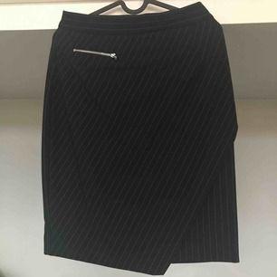 Snygg kritstrecksrandig kjol med dekorativ dragkedja på framsidan. Kjolen går halvvägs ner på låren och sitter högt i midjan. Mörkt marinblå!