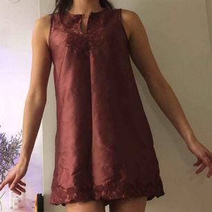 Rostrött glansigt nattlinne/klänning från Indiska i 100% polyester. Sträcket i mitten är endast där då den legat ihopvikt.  (っ◔◡◔)っ MÅTT: Byst: 43cm Längd: 79cm