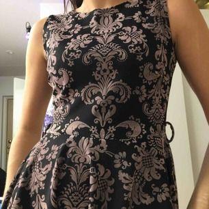 Svart/brun klänning i tung och tjock polyester med rosa paisley-detaljer i viskosliknande material. Hål i midjan som lätt kan sys igen (bild 3).  (っ◔◡◔)っ MÅTT: Byst: 40cm Längd: 81cm Midja: 36cm