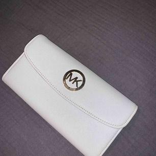 En gammal oäkta Michael Kors plånbok som aldrig har kommit till användning! Bjuder på frakt.