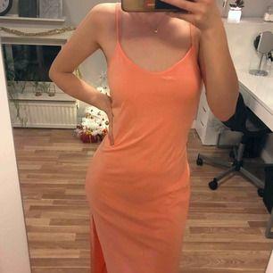 Ljust korall-orange långklänning med slitsar i sidorna. Djupare urringning bak. Passar bra på mig som vanligtvis bär S, dock lite kort (167 cm). Passar även en M om man vill att den sitter tajtare. Vid köp av flera plagg samfraktar jag, så in och kika!💕