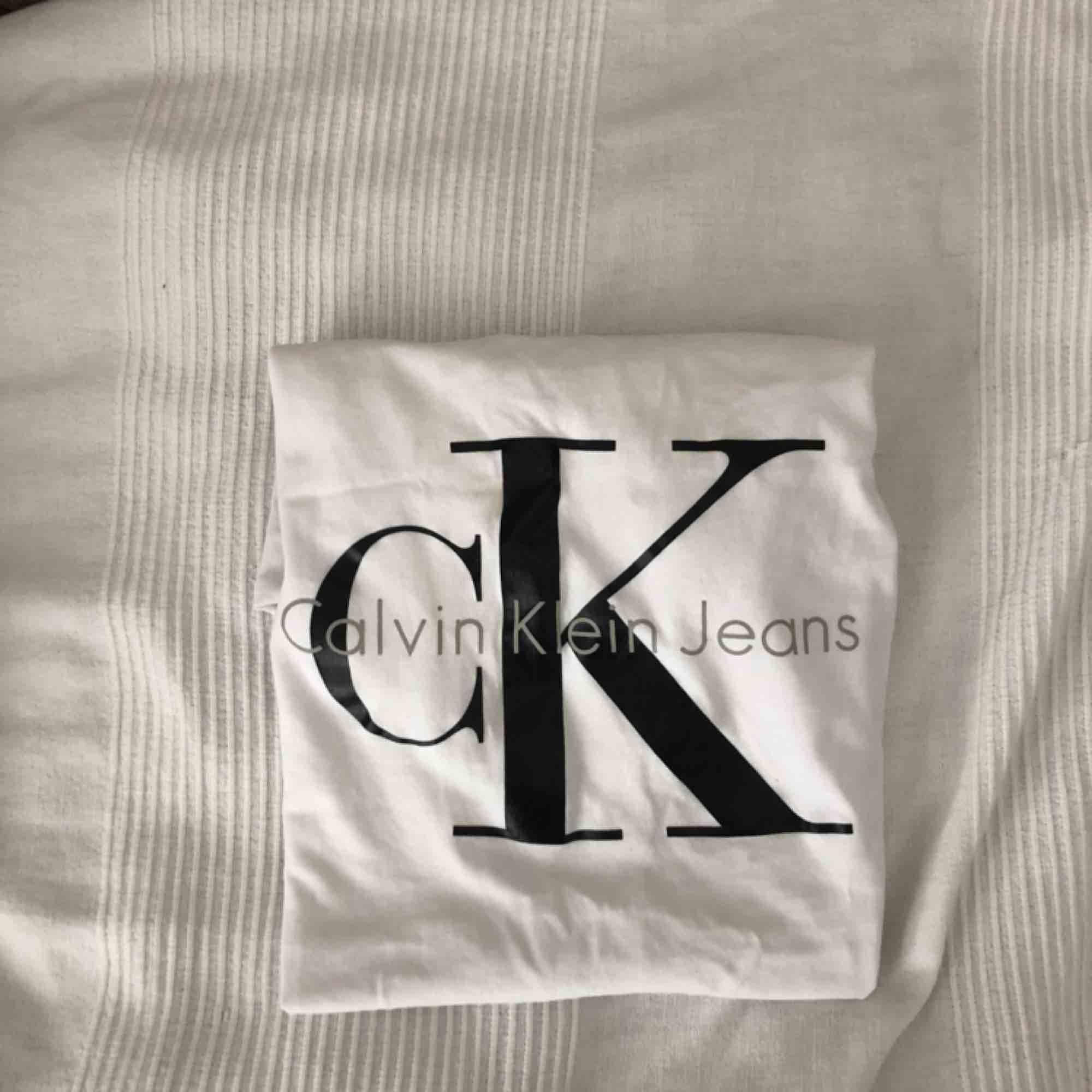 Vit Ck T-shirt med svart tryck, använd ett par gånger men fortfarande i bra skick, (den är äkta). T-shirts.