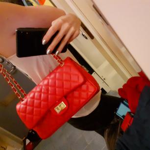 Röd quiltad väska i Chanelinspirerad modell med vinröda inre detaljer<3 Fint skick! Ca 27cm bred, höjd:ca 16cm. Säljes pga inte kommit till användning. Frakt: 63:- Spårbart