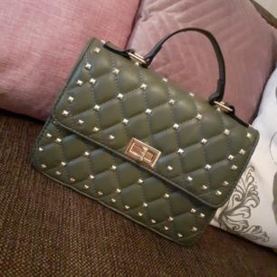 Militärgrön valentinoinspirerad väska med guldiga nitar. Fint skick! Säljes pga kommer ej till användning. Frakt: 63:- spårbart.