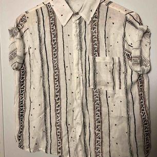 Vit T-shirtskjorta med grå och vinröda mönster. Kan mötas upp i Stockholm eller Västerås. Betalning sker när vi ses.