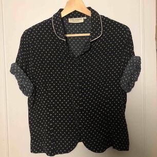 Svart/mörkblå skjorta med guldblommor och guldkant på kragen. Köpt secondhand men märket är Lindex. Matchade den ofta med svarta jeans och Docs. Kan mötas upp i Stockholm eller Västerås. Betalning sker när vi ses!