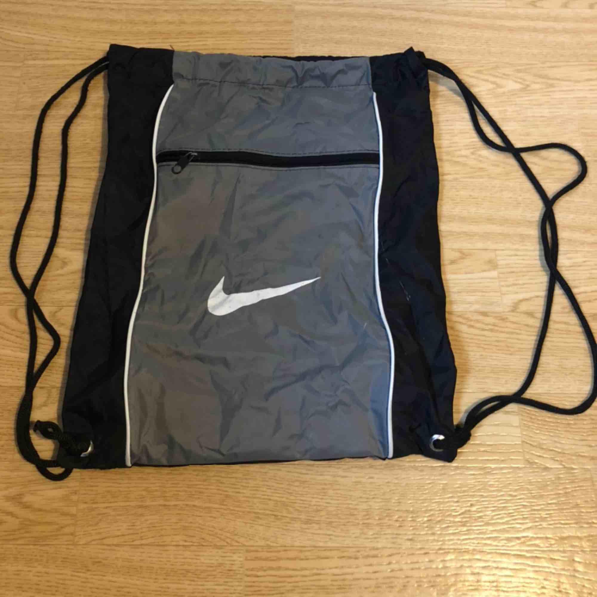 Gympapåse från Nike/  Grå med vit logga. Väskor.