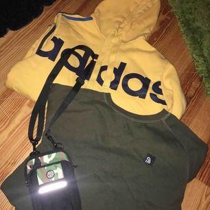 En gul adidas hoodie och en grön sweatshirt med svart tryck på ryggen. Väskan får man med på köpet. :)