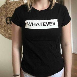 """En basic t-shirt i Svart med tryck på bröstet med texten """"whatever"""". I gott skick!  Säljs på grund av att den inte kommer till användning längre.  Köparen står för frakt, annars kan jag mötas upp i Helsingborg :)"""