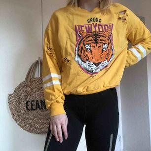 En gul tröja med slitningar och tryck på magen/bröstet. Använd några få gånger och så gott som ny! Kan mötas upp i Helsingborg, annars så står köparen för frakten.