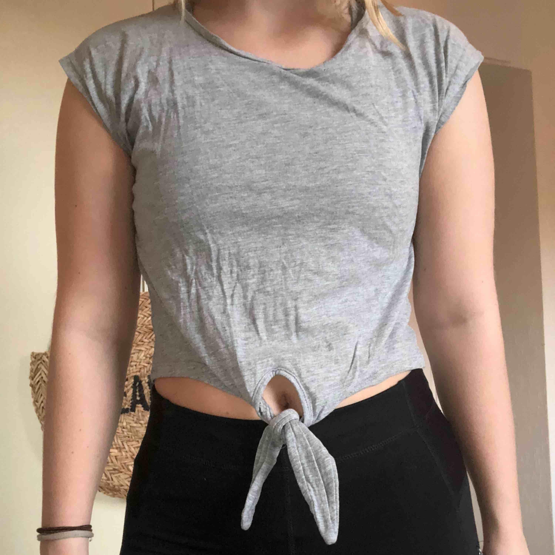 En grå t-shirt med knyte längst ner. Använd ett fåtal gånger bara! Kan mötas upp i Helsingborg, annars står köparen för frakten. (Ca 18kr). . T-shirts.