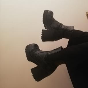 Svarta platåboots i stl 39 köpta secondhand. Gjorda i äkta skinn, dock ganska slitna i skinnet. Har kört på med massa svart skokräm då och då för att fräscha upp skorna men den tog slut och har inte orkat köpa ny. Tycker skorna är asfeta ändå så spelar ingen roll för mig att de inte ser nya ut. Frakt 63 kr.