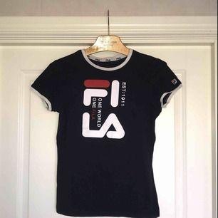 Säljer en snygg Fila T shirt i marinblå! Står storlek M i den men sitter absolut mer som en XS/S. Lite sportig modell som är väldigt stretching och bekväm! Aldrig använd så säljes till ett väldigt bra pris!